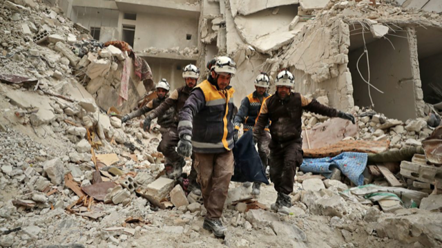 The white helmet organization carries a body from the rubble